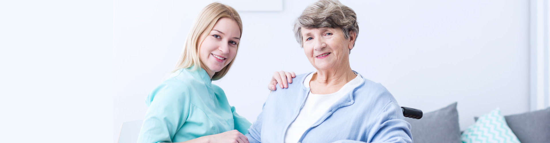 smiling caregiver and her old woman patient sitting on her wheel chair