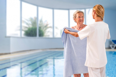 female caregiver giving towel to her patient