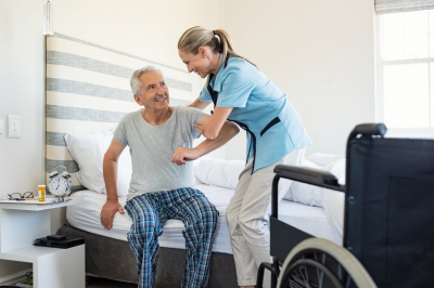 smiling caregiver assisting to her patient to stand