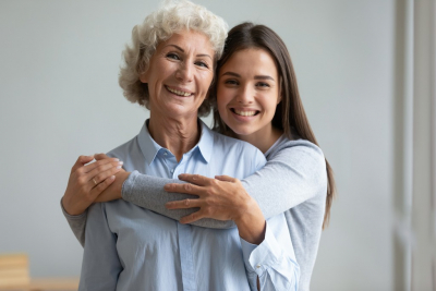 smiling young women hugging to her grand mother
